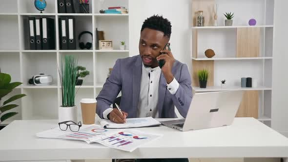 30-Aged Black-Skinned Businessman in Stylish Wear Writing Important Marks Into Financial Report
