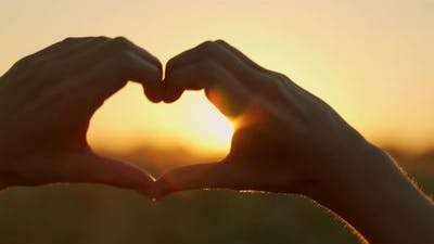 The Silhouette of a Hand in the Shape of a Love Heart at Sunset