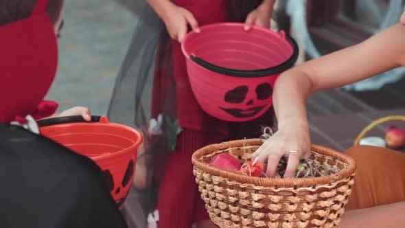 Fröhliche Frau, die Süßigkeiten zu Trick-oder-Behandler