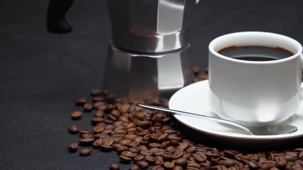 Tasse Espressokaffee und Mokka-Kaffeemaschine auf gerösteten braunen Kaffeebohnen auf Betonhintergrund