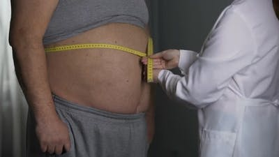 Nutritionist Measuring Waistline of Overweight Male Patient, Dieting and Obesity