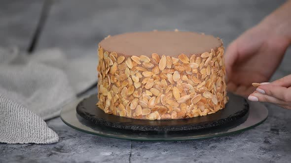 Female Pastry Chef Prepares a Cake and Decorates It with Almond Flakes.
