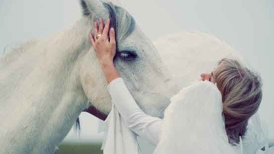 Cloudy Sky in the Background of an Angel Petting a White Horse, Animals,