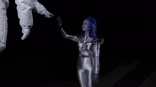Thumbnail for Astronaut and Alien Stretch To Each Other with Their Hands