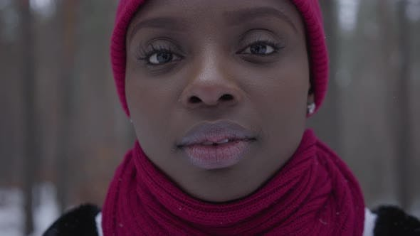 Cover Image for Close-up Portrait of an African American Girl Dressed Warm Wearing a Red Hat and a Red Scarf