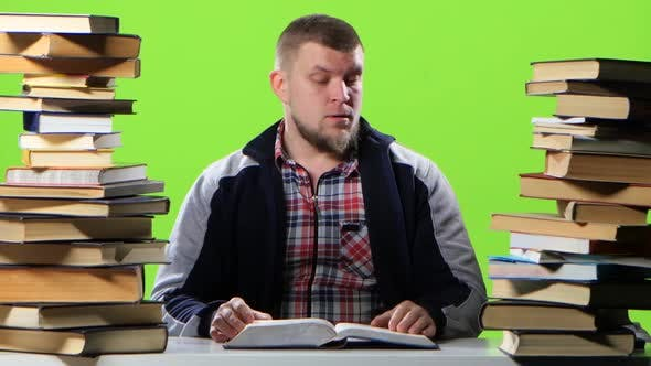 Thumbnail for Man Sitting at His Desk Leafing Through a Textbook. Green Screen