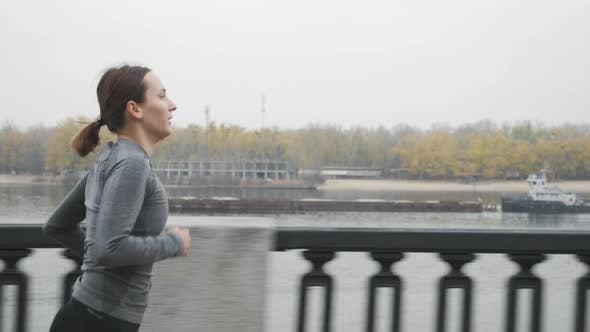 Motivated Fit Sports Woman Hard Breathing and Intense Training Outdoor Along Industrial City River