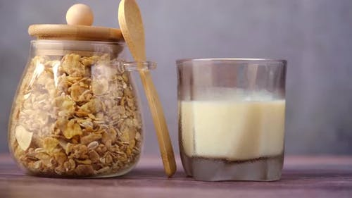 Cereal Breakfast in Glass Jar and Milk on Table