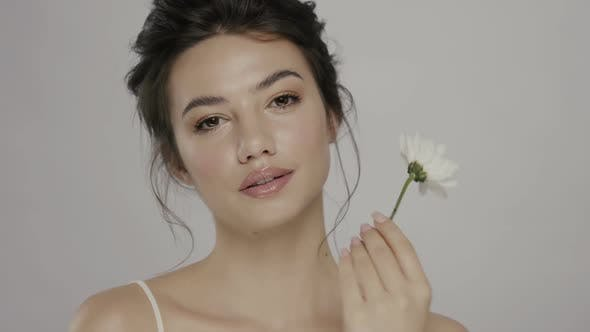 Thumbnail for Pretty Girl with Clean Skin Touching Her Face with Fresh White Flower