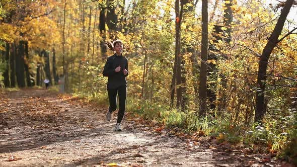 Thumbnail for Young woman jogging through forest