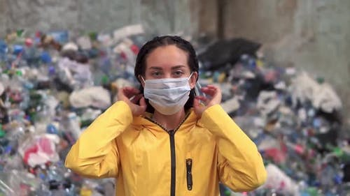 Young Woman Worker Putting on a Mask and Protective Eyeglasses