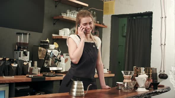 Thumbnail for Young Female Coffe Shop Owner Have a Phone Call Using Smartphone in Cafeteria