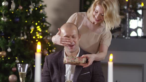 A Husband For Christmas.Caucasian Wife Giving Husband Christmas Gift At Romantic