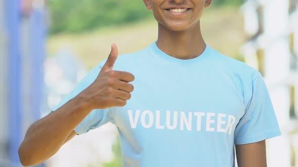 Smiling volunteer showing thumbs up, humanitarian help