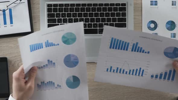 Thumbnail for Office Manager Comparing Statistical Reports of Company Typing in Data to Laptop