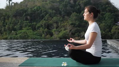 Young Woman Sits in a Lotus Position Near the Rooftop Pool