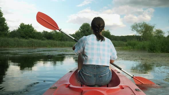 Thumbnail for Young woman is paddling in kayak on river against beautiful landscape. Travel. Tourism.