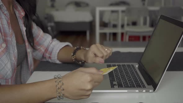 Thumbnail for Cropped Shot of Young Woman with Long Hair Typing Card Number on Laptop.