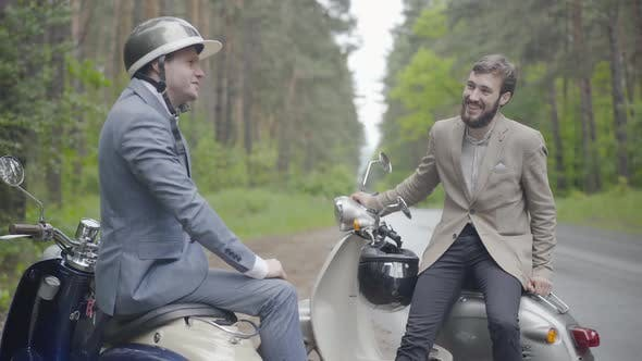Thumbnail for Two Confident Positive Caucasian Men Sitting on Retro Scooters on Countryside and Talking. Portrait