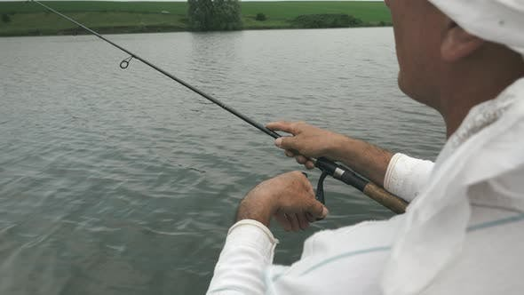 Fisherman catches fish. Man fishing with spinning rod on lake. Fishing concept
