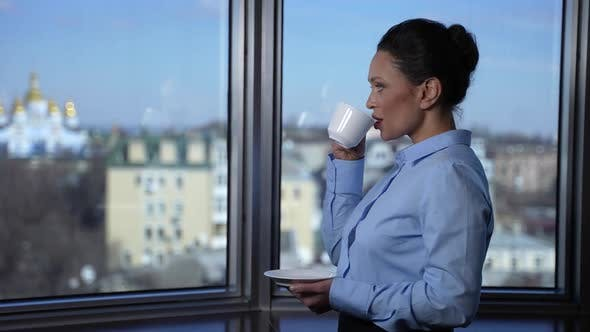 Confident Businesswoman Drinking Coffee By Window