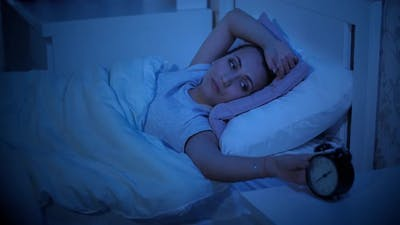 Woman with Insomnia Looks at the Alarm Clock