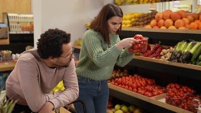 Sad Man Looking at Woman Choosing Vegan Products