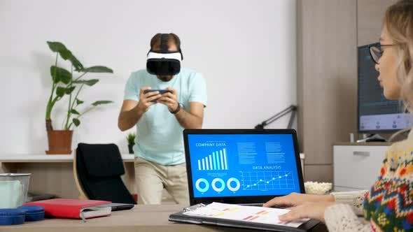 Thumbnail for Man Playing with VR Headset While His Girlfriend Works on the Computer in the Same Room