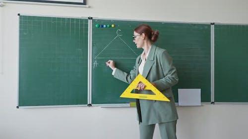 Porträt eines modernen Lehrers, der in die Kamera blickt und Pädagoge in Brille mit Lineal in Händen sagt