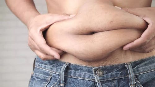 Man's Hand Holding Excessive Belly Fat Overweight Concept