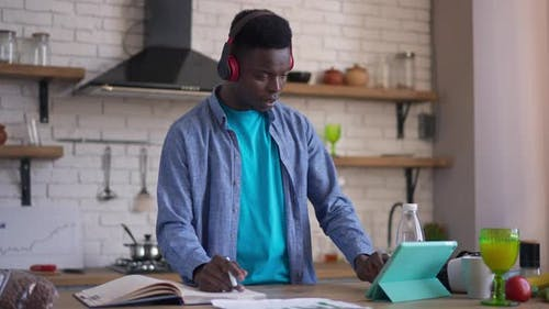 Busy Focused Young Man in Headphones Writing in Sketchpad with Pen Scrolling Tablet Screen Standing