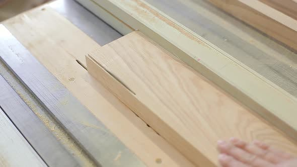 Carpenter Sawing Plank on a Saw Circulation in Workshop