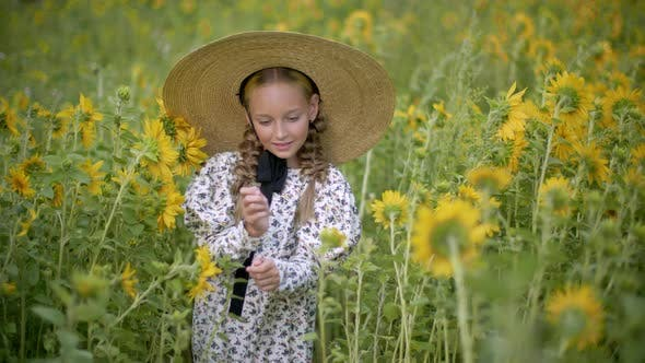 Thumbnail for Romantic Girl with Two Braids and Straw Hat Walking on Blooming Sunflowers Meadow. Rustic Girl in