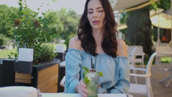 Thumbnail for Beauiful Woman Sitting in Outdoor Restaurant and Sip Mojito Dring in Summer Hot Day