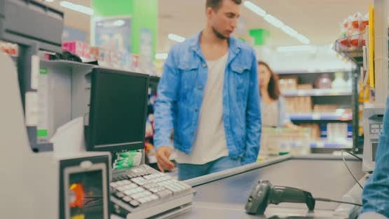 Young Woman Walks Up to the Checkout Counter and Spreads the Goods