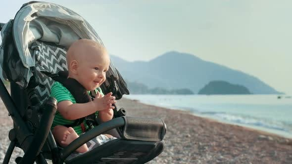Thumbnail for Happy Baby Clapping Hands in Stroller at Sea Beach. Little Boy Clapping Hands