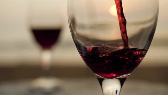 Thumbnail for Close Up Pouring Red Wine Glass at Sunset on Seaside View Deck Landscape. Ocean Beach Waves Macro