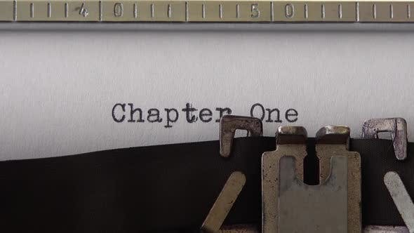 Typing phrase Chapter One on retro typewriter. Close up.
