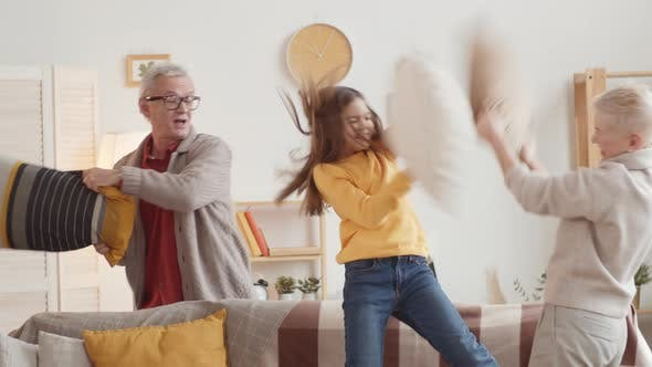 Thumbnail for Caucasian Grandparents Having Pillow Fight with Granddaughter at Home