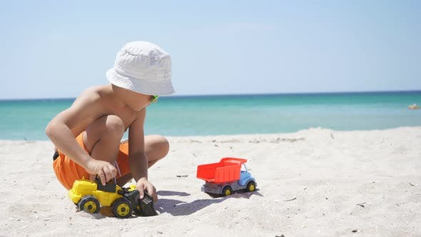 Happy Kid Playing with Cars on the Beach on the Horizon Azure Sea and Blue Sky