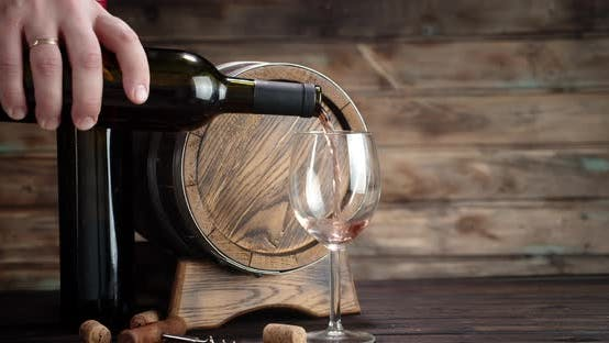 Thumbnail for A Man's Hand Pours Wine Into a Glass. On a Wooden Background.