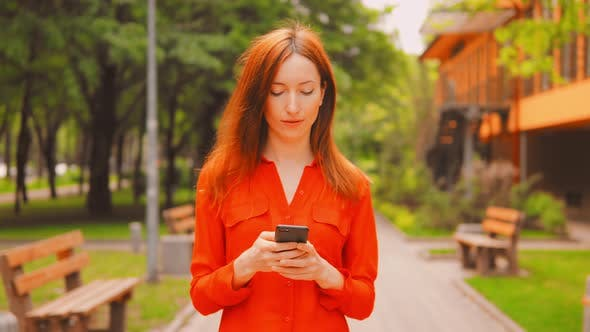Thumbnail for Redhead Woman Scrolls Touch Screen on Smartphone Outdoor