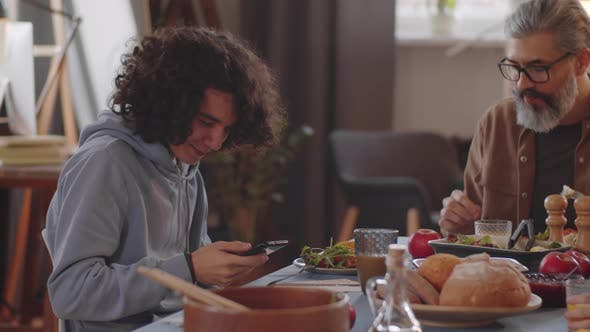 Teen Boy Using Smartphone at Family Dinner