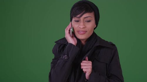 Fashionable woman in black overcoat on cellphone on green screen