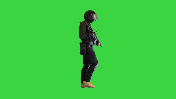 Swat Operator with Assault Rifle Walking on a Green Screen Chroma Key