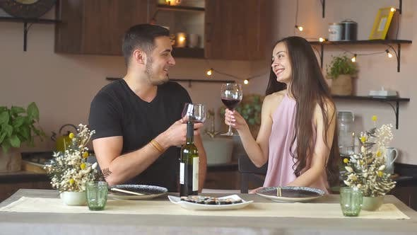 Happy couple enjoying spending time together drinking red wine. Dating at home.