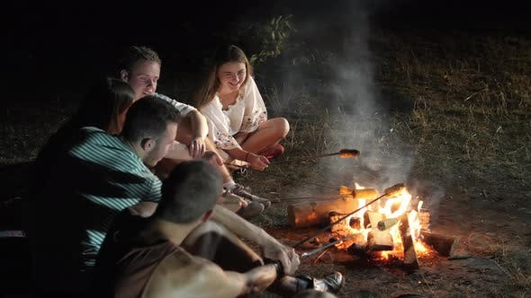 Thumbnail for Friends at the campfire with corn on cob
