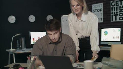 Satisfied Woman Boss Praising Employee for Good Work in Dark Office