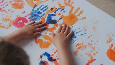 Little Girl with Paints on Her Hands Draws on White Paper