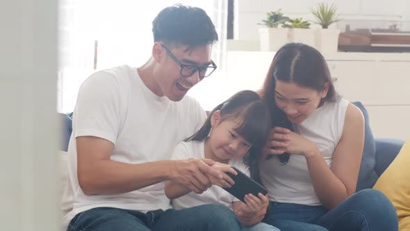 Happy Asian family dad, mom and daughter playing funny game online on smartphone.